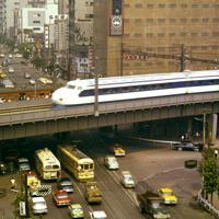 10月1日の開業を前に、新橋駅付近を走行する東海道新幹線の試運転車両。高架下の外堀通り(下)には都電が走る=1964年9月