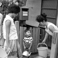 やかんやバケツを手に給水車の到着を待つ親子。8月6日から第4次制限の1日5時間給水が実施された。200台ある自衛隊の給水車が唯一の水源で、井戸を掘る家まで現れ、「東京オリンピック渇水」「東京砂漠」と呼ばれるようになった=渋谷区で1964年8月