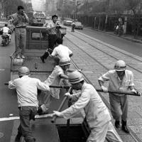 渇水による給水制限のため、銀座八丁目で水道本管のバルブを締める作業員=1964年7月21日、松野尾章撮影