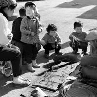 1本の針金から三輪車やピストル、リヤカーなどを作る針金細工師(右)を囲む子供たち=東京都内で1963年12月、川辺信一撮影