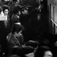朝7時屋半ごろからはじまる新宿駅のラッシュアワーは8時20分頃に頂点に達し、ホームはひどく混雑する。ホームにはドア近くの乗客を電車から引き離す「はぎ取り部隊」と呼ばれる職員(中央)が働いていた=新宿駅で1964年1月、中西浩撮影