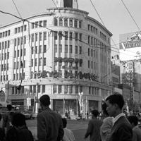 銀座4丁目交差点。中央にある「和光」の壁面に「WELCOME TO THE TOKYO OLYMPICS」の文字が掲げられた。道路の上には都電の架線が見える=中央区で1964年10月