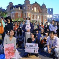 花やプラカードを手に集まった人たち=大阪市北区で2019年5月11日午後7時21分、望月亮一撮影