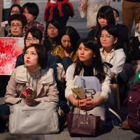 「フラワーデモ」で花を持ってスピーチを聞く参加者ら=JR東京駅前で2019年5月11日午後7時12分、北山夏帆撮影