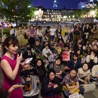 「フラワーデモ」に参加してスピーチを聴く人々=JR東京駅前で2019年5月11日午後7時44分、北山夏帆撮影