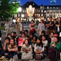 性犯罪の実態を訴える「フラワーデモ」で、主催者のスピーチを聞く参加者ら=JR東京駅前で2019年5月11日午後7時12分、北山夏帆撮影