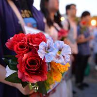 性暴力に抗議して花やプラカードを手に大勢の人たちが集まった=大阪市北区で2019年5月11日午後7時10分、望月亮一撮影
