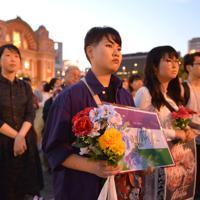 花やプラカードを手に集まった人たち=大阪市北区で2019年5月11日午後7時16分、望月亮一撮影