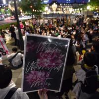 性犯罪の実態を訴える「フラワーデモ」で、プラカードを掲げて被害女性の話を聞く参加者ら=JR東京駅前で2019年5月11日午後7時41分、北山夏帆撮影