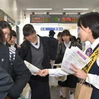 通学中の女子高生たちに啓発リーフレットを配る京都銀行西舞鶴支店の行員ら=京都府舞鶴市のJR西舞鶴駅で、行方一男撮影