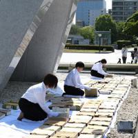 原爆慰霊碑の前で原爆死没者名簿の「風通し」をする市職員ら=広島市中区で2019年5月15日午前9時4分、大西達也撮影