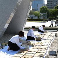 原爆慰霊碑の前で原爆死没者名簿の「風通し」をする広島市職員ら=広島市中区で2019年5月15日午前9時4分、大西達也撮影