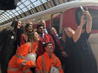 London North Eastern Railway (LNER) staff members take a commemorative photo in front of the new high-speed train