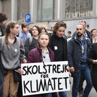 「気候のためのスクールストライキ」と書かれた手作りのボードを手にデモ行進するグレタ・トゥーンベリさん(中央)=ブリュッセルで2019年2月21日午後2時46分、八田浩輔撮影