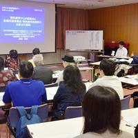 慢性疲労症候群の治療法の開発などについて講演する渡辺恭良さん(左奥)=神戸市中央区雲井通5の市勤労会館で、谷田朋美撮影