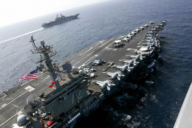 In this Friday, May 17, 2019, photo released by the U.S. Navy, the USS Abraham Lincoln sails in the Arabian Sea near the amphibious assault ship USS Kearsarge. Commercial airliners flying over the Persian Gulf risk being targeted by