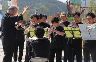 鎮魂の思いを込めて指揮する杉木峯夫さん(左)と、トランペットを奏でる参加者たち=陸前高田市高田町のアバッセたかた駐車場特設会場で