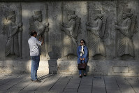In this May 18, 2019 photo, a couple takes photos with bas reliefs of ancient Persian soldiers in an old neighborhood in downtown Tehran, Iran. (AP Photo/Vahid Salemi)