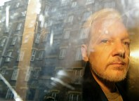 In this May 1, 2019 file photo, buildings are reflected in the window as WikiLeaks founder Julian Assange is taken from court, where he appeared on charges of jumping British bail seven years ago, in London. (AP Photo/Matt Dunham)