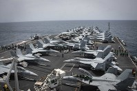 In this May 19, 2019, photo released by the U.S. Navy, sailors partake in a foreign object and debris walk-down on the flight deck of the Nimitz-class aircraft carrier USS Abraham Lincoln in the Arabian Sea. (Mass Communication Specialist 3rd Class Garrett LaBarge/U.S. Navy via AP)