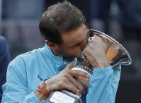 Rafael Nadal of Spain kisses his trophy after winning against Novak Djokovic of Serbia at the end of their final match at the Italian Open tennis tournament, in Rome, on May 19, 2019. (AP Photo/Gregorio Borgia)