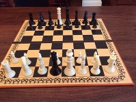 A chessboard set up for Damian Flanagan's son's alternate version of chess, with the queens held captive by the opposing side.