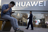 A man uses two smartphones at once outside a Huawei store in Beijing on May 20, 2019. (AP Photo/Ng Han Guan)