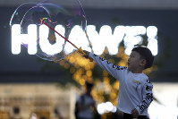 In this photo taken on May 20, 2019, a child plays with bubbles near the logo for tech giant Huawei in Beijing. (AP Photo/Ng Han Guan)