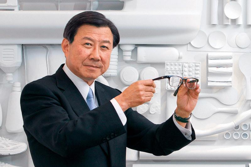 持っているのはスイッチ一つで屈折率が切り替わる遠近両用レンズを装着させたメガネ Photo 中村琢磨(東京都港区の本社で)