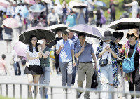 Tourists use sun umbrellas in the scorching summer heat, in Tokyo's Chiyoda Ward, in this June 18, 2016, file photo. (Mainichi/Kimi Takeuchi)