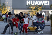 In this photo taken on May 20, 2019, residents enjoy a cool evening near a Huawei store in Beijing. (AP Photo/Ng Han Guan)