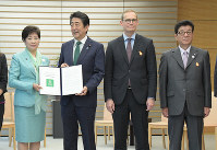 Tokyo Gov. Yuriko Koike, left, passes the Urban 20 (U20) Tokyo Mayor's Summit policy proposals to Prime Minister Shinzo Abe, second from left, at the prime minister's office in Chiyoda Ward, Tokyo, on May 22, 2019. (Mainichi/Masahiro Kawata)