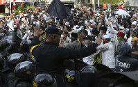 Indonesian police officers block supporters of Indonesian presidential candidate Prabowo Subianto during a rally outside the Elections Supervisory Agency (Bawaslu) building in Jakarta, Indonesia, on May 21, 2019. (AP Photo/Achmad Ibrahim)
