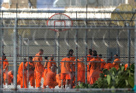 In this July 4, 2015, file photo, prison inmates stand in the yard at Arizona State Prison-Kingman in Golden Valley, Ariz. (Patrick Breen/The Arizona Republic via AP)