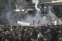 Indonesian riot police officers fire tear-gas canisters to disperse supporters of Indonesian presidential candidate Prabowo Subianto in Jakarta, Indonesia, on May 22, 2019. (AP Photo)