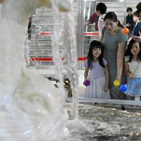メッセージを書いたカラーボールを噴水に投げ込む家族連れ=大阪市北区で、小松雄介撮影
