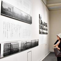 新着資料展で、岸田貢宜さんが撮影した写真に見入る来館者=広島市中区の原爆資料館で、小山美砂撮影