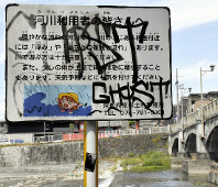 A public sign near the Kamogawa River in Kyoto's Higashiyama Ward urging people to take caution in the water is seen graffitied, on May 22, 2019. (Mainichi/Kanae Soejima)