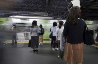 Commuters wait to get on a train at a station on May 22, 2019, in Tokyo. (AP Photo/Eugene Hoshiko)