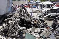 Somalis walk near the wreckage after a suicide car bomb attack in the capital Mogadishu, Somalia on May 22, 2019. (AP Photo/Farah Abdi Warsameh)