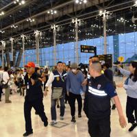 タイから日本への移送のため警察官に囲まれながら歩く振り込め詐欺グループのニット帽をかぶった容疑者の男(中央)=スワンナプーム国際空港で2019年5月24日午前5時53分、西脇真一撮影