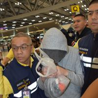 タイから日本に移送されるため警察官らに囲まれて歩く振り込め詐欺グループの容疑者の男(中央)=スワンナプーム国際空港で2019年5月24日午前5時52分、西脇真一撮影