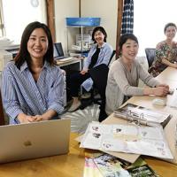 笑顔の絶えない職場で、仲間とフリーペーパーを編集する小西美由紀さん(左端)=大阪府箕面市で