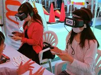 Two women use VR headsets to experience dangerous situations that could occur when looking at a smartphone while riding a bicycle, in the city of Musashino, Tokyo, on May 23, 2019. (Mainichi/Taketo Hayakawa)