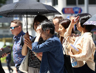 People walk under the hot summer sun in the capital's Minato Ward shortly after midday on May 24, 2019. (Mainichi/Junichi Sasaki)