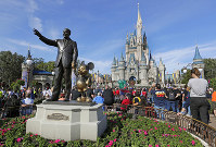 In this Jan. 9, 2019 file photo, guests watch a show near a statue of Walt Disney and Mickey Mouse in front of the Cinderella Castle at the Magic Kingdom at Walt Disney World in Lake Buena Vista, part of the Orlando area in Florida. (AP Photo/John Raoux)