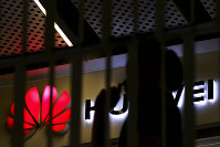 A man walks by a Huawei retail shop behind a handrail inside a commercial office building in Beijing, on May 21, 2019. (AP Photo/Andy Wong)