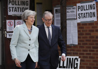 Britain's Prime Minister Theresa May and her husband Philip leave a polling station after voting in the European Elections in Sonning, Britain, on May 23, 2019. (AP Photo/Frank Augstein)