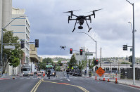 In this May 21, 2019 photo, two drones fly above Lake Street in downtown Reno, Nevada, as part of a NASA simulation to test emerging technology that someday will be used to manage travel of hundreds of thousands of commercial, unmanned aerial vehicles (UAVs) delivering packages. (AP Photo/Scott Sonner)
