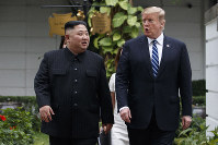 In this Feb. 28, 2019 file photo, U.S. President Donald Trump and North Korean leader Kim Jong Un take a walk after their first meeting at the Sofitel Legend Metropole Hanoi hotel, in Hanoi, Vietnam. (AP Photo/Evan Vucci)